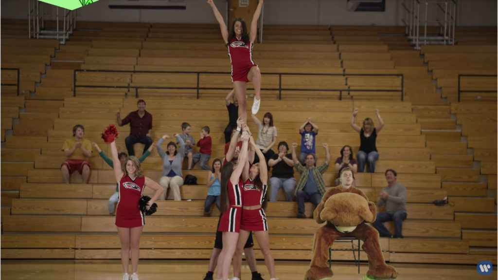 A high school gym. There are people in the bleachers and cheerleaders doing some kind of lift. Justin Bieber sits in a folding chair beside them in the teddy bear suit with the head off.