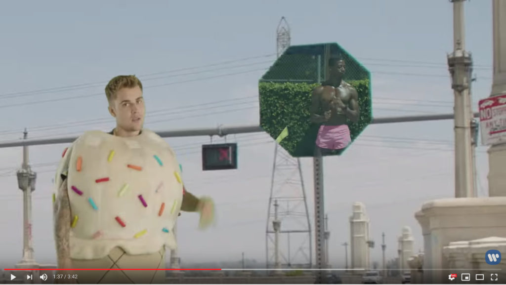 Now, Beebs is dressed like an ice cream cone, superimposed over a street with a traffic signal in the background and a stop sign that has been made into a window on the pool party scene, framing a sexy, shirtless, absolutely fucking ripped black guy.