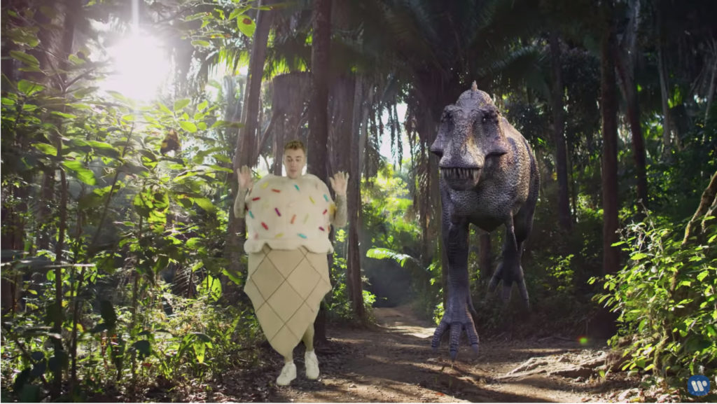 Justin Bieber dancing in his ice cream cone costume in front of a charging T-Rex.
