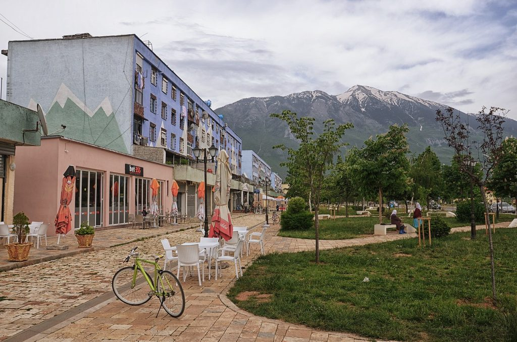 Photo of a clean, modern street in Kükes. There is some kind of business on the lower level of a building that is painted with a mural of mountains. There is also a mountain visible in the background. A park with a bicycle and cafe tables and chairs are on the right of the street.