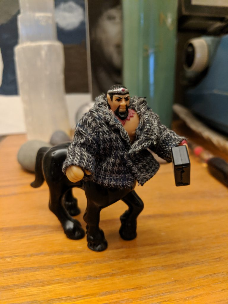 A small centaur toy with a black horse body, tan man body, goatee, and little painted-on crown. Bronwyn Green sewed him a tiny houndstooth business jacket and given him a briefcase.