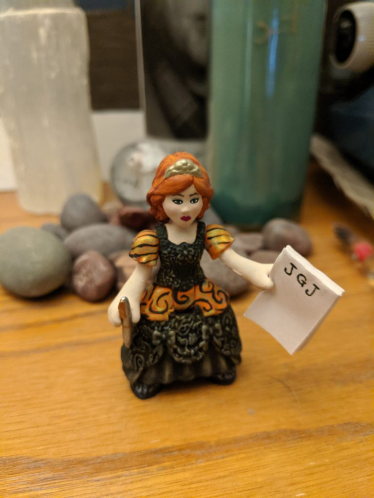 A small princess figure with red hair and a notepad with JGJ written across the top and a pen in her other hand.