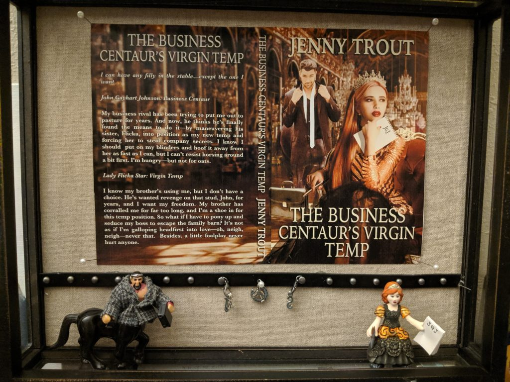 A shadow box containing a cover flat (described later) for The Business Centaur's Virgin Temp by Jenny Trout, the two action figures standing beneath it, and various charms hanging from push pins on a strip of studded leather across the lower quarter of the box.