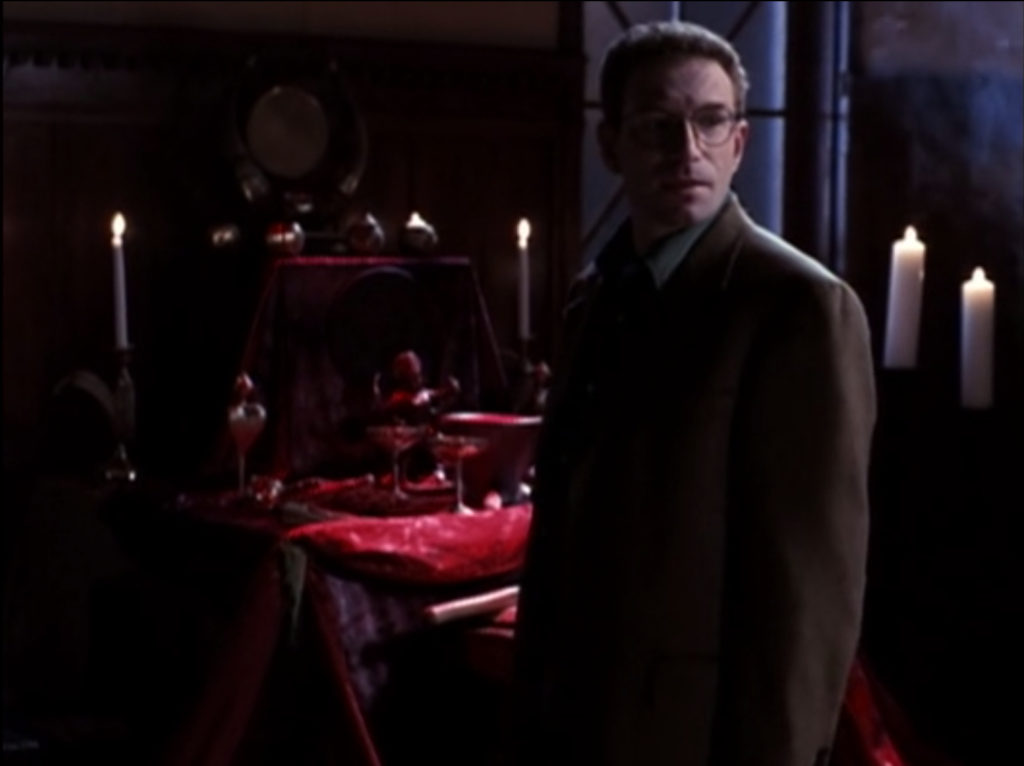 The lawyer guy is standing in front of a nebulous kind of altar thing. It's all red and has bunch of candles around it, and you can kind of make out there are various goblets and metaphysical tools on it. But just barely.