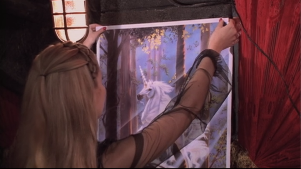 Harmony hanging up a unicorn poster in the crypt