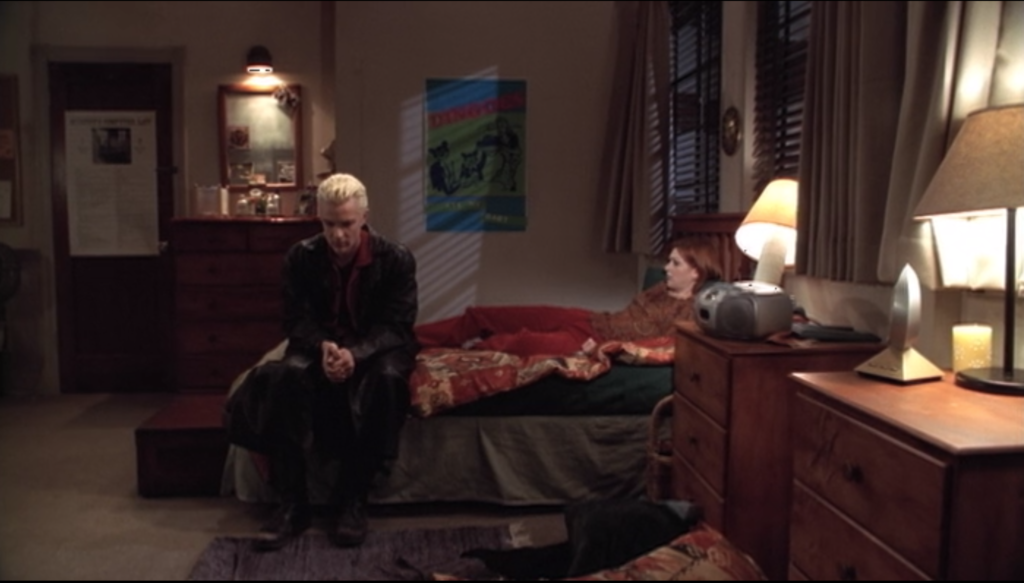 Spike is sitting on the end of Willow's bed, looking ashamed, while Willow sits against the pillows looking sympathetic.