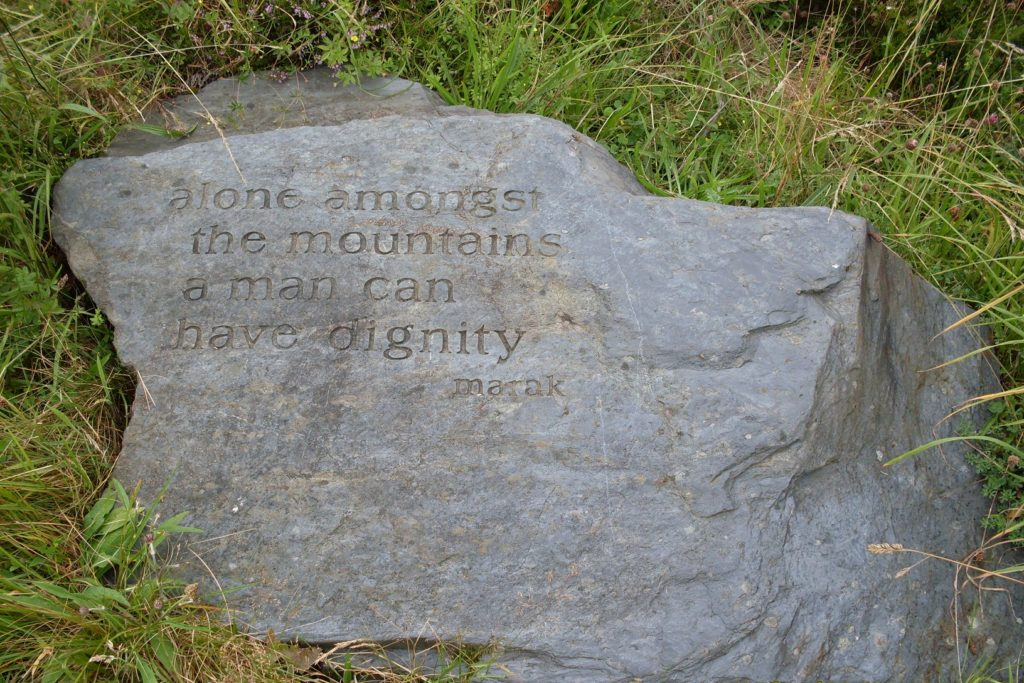 "A stone etched with the quote, ""Alone amongst the mountains a man can have dignity. -Marak"""