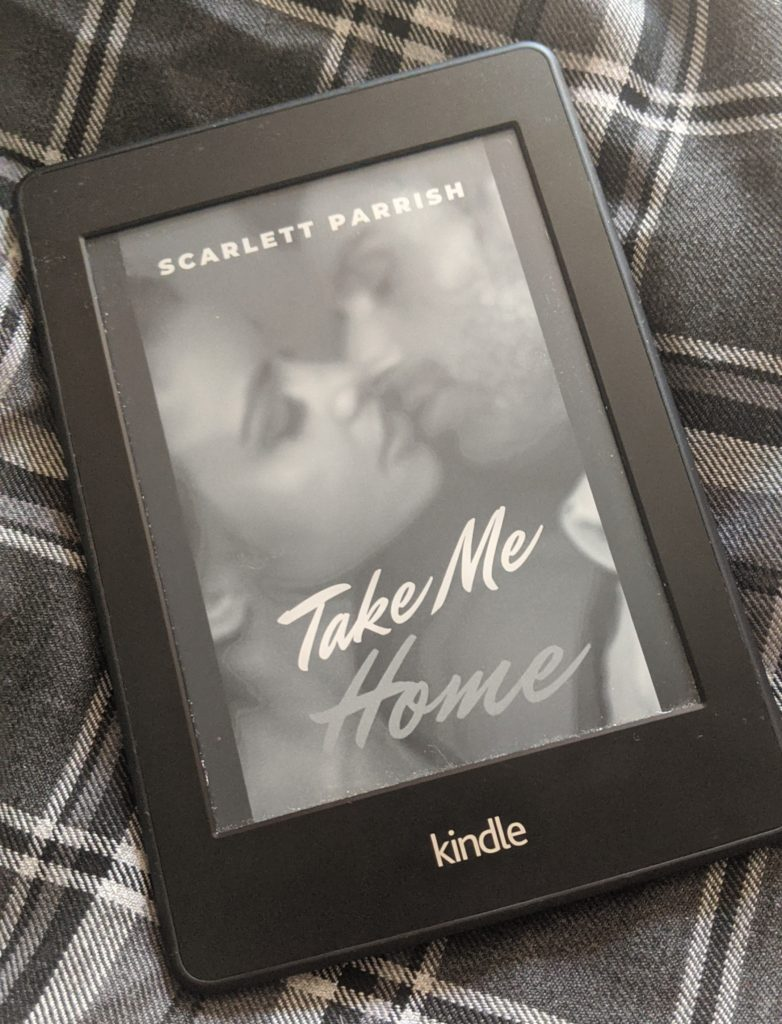 My Kindle with the cover of Take Me Home by Scarlett Parrish displayed. The cover shows a slightly out-of-focus couple kissing. The kindle is lying on a tartan background.