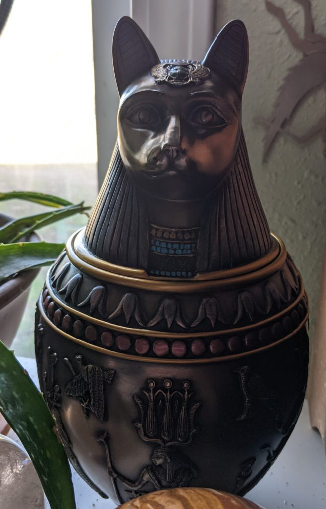 The urn is in the style of an ancient egyptian coptic jar with Bast's head on it.