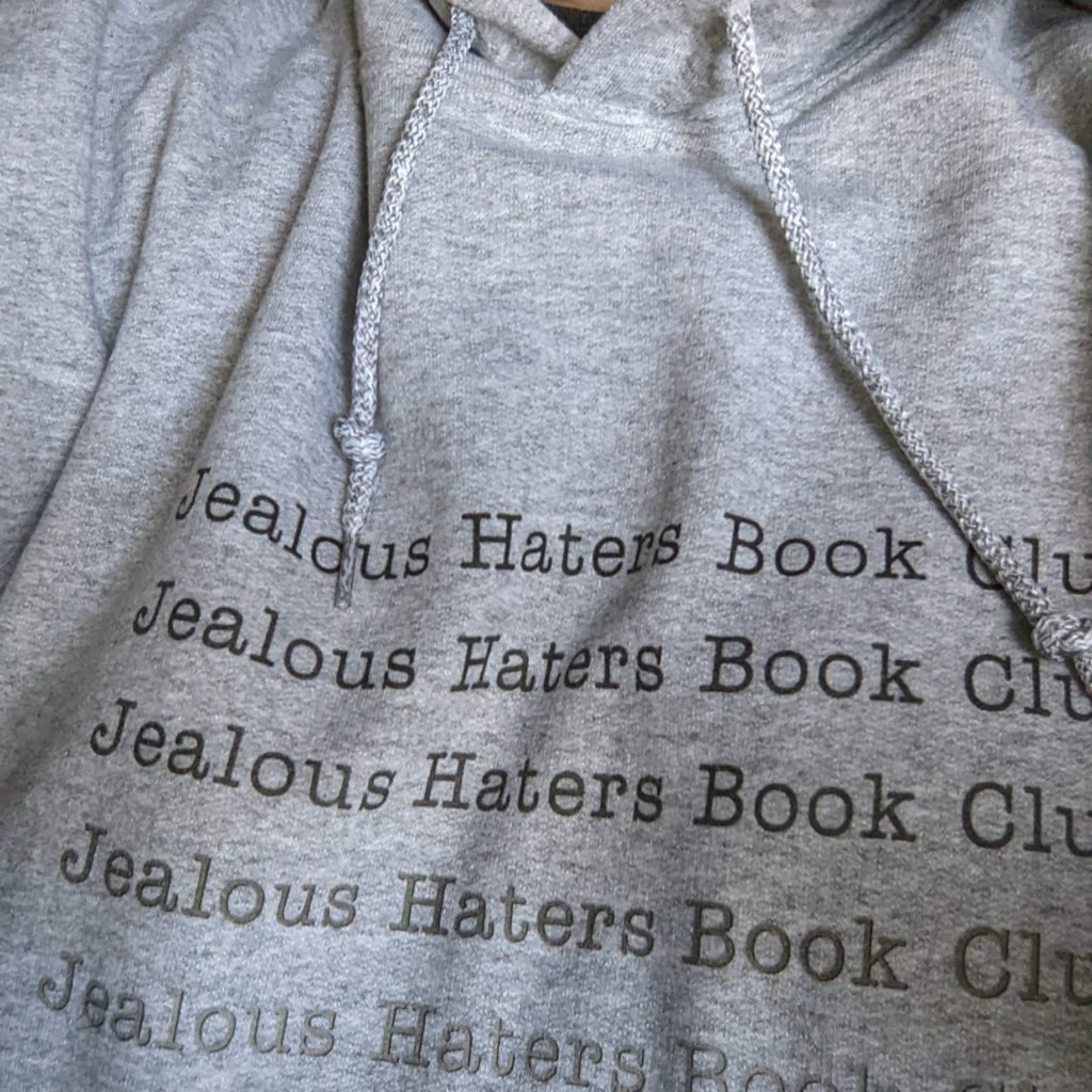 A close of a hoodie, with the collar and string things showing. Jealous Haters Book Club is printed multiple times in a column, again in varying shades of gray